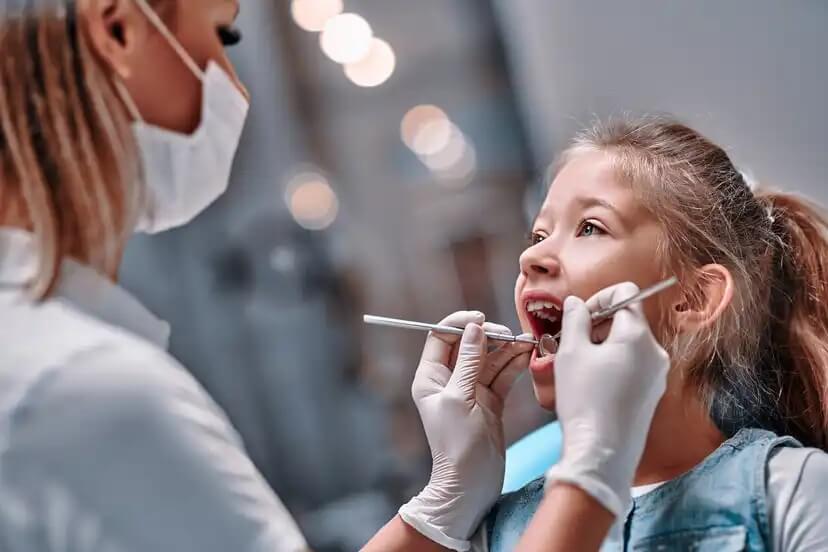 Menina no dentista para descobrir os maus hábitos para os dentes das crianças.
