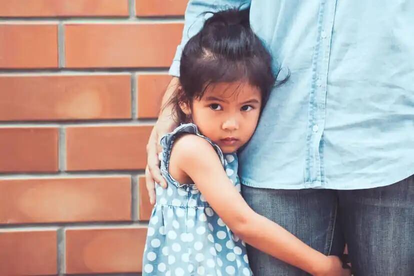 Menina com medo, abraçando a perna do pai.