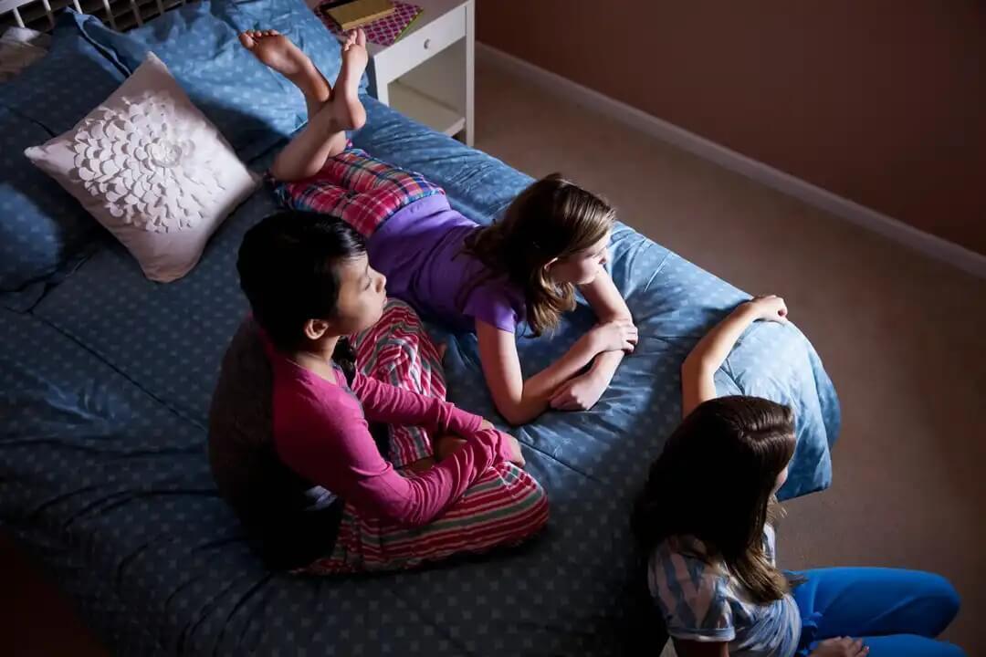 Crianças assistindo filmes em uma festa do pijama.