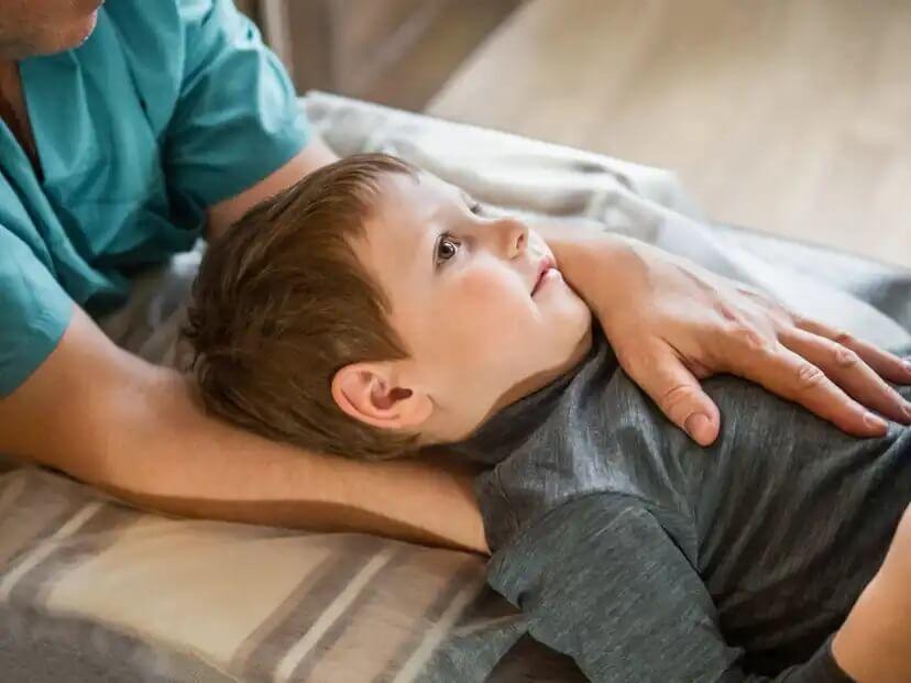 Criança em fisioterapia infantil com dor de pescoço.