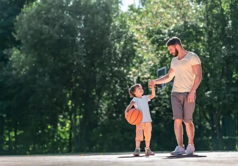 Pai e filho praticando esportes juntos para promover a empatia.