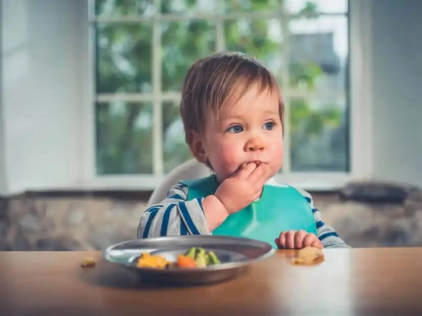 Bebê comendo sozinho com as mãos.