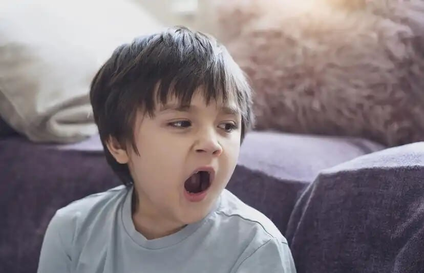 Menino cansado bocejando.