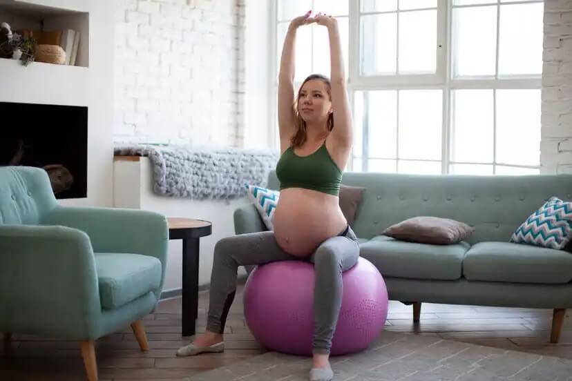 Mulher fazendo exercícios na bola medicial durante a gravidez.